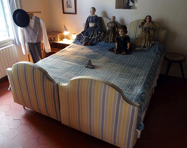 アンティーク人形が置かれた寝室のベッド。